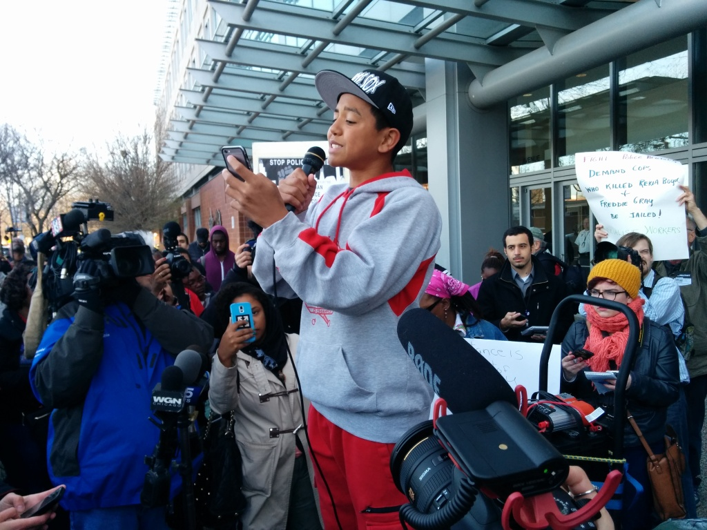 A 14 year old poet name Jalen performs outside police headquarters before a crowd of hundreds. (Photo: Kelly Hayes)